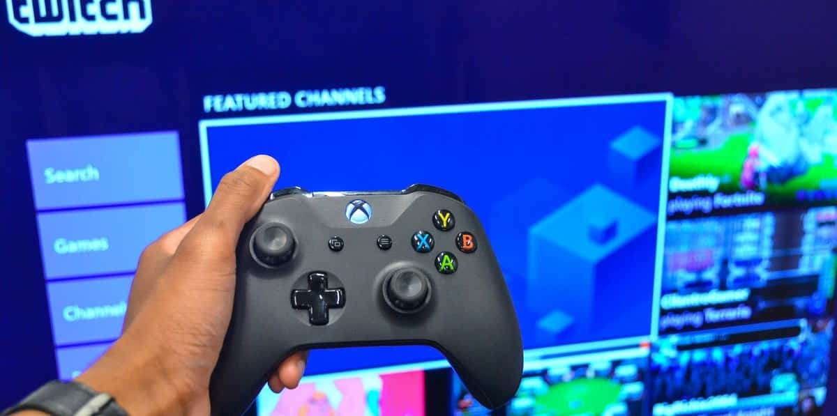 man holding a xbox one controller in front of twitch streaming screen