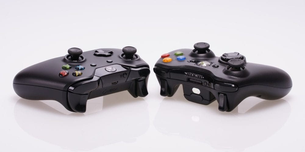 two xbox controllers next to each other